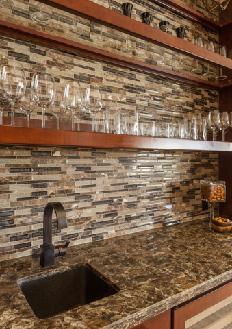 COURTESY ROOM RESOLUTIONS Open wood shelves, granite counter and colorful glass tiles combine for an elegant home bar.