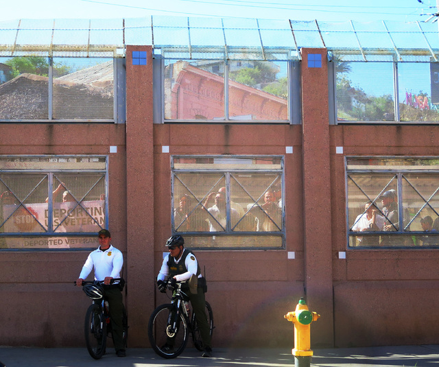 A group of people who identified themselves as U.S. military veterans stand in Mexico looking through the border fence as presidential candidate Bernie Sanders made a visit to the border in Nogale ...
