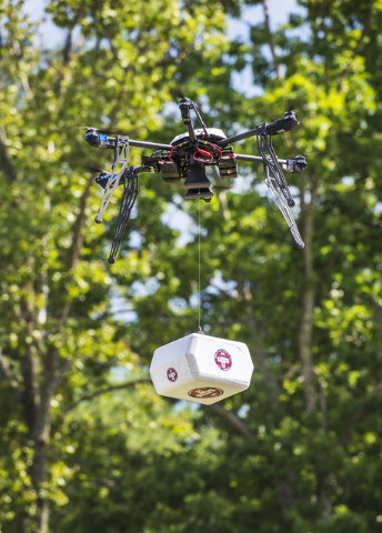 A Flirtey drone flies above the Wise County Fairgrounds while lowering a package of prescription medication at the Remote Area Medical (RAM) clinic in Wise County, Va.  (Tim C Cox/The Bristol Hera ...