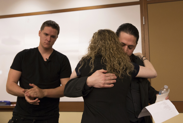 """Christopher Aaron, former counter-terrorism officer in the Central Intelligence Agency, hugs lawyer Jessalyn Radack during a symposium titled """"Inside Drone Warfare: Perspectives of Whistleblowers, ..."""