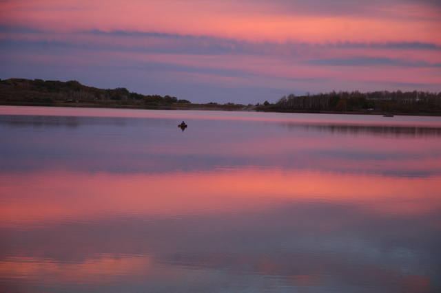 A float-tubing angler enjoys a solitary moment at sunset on Kolb Reservoir in Southern Utah. Photo by Doug Nielsen