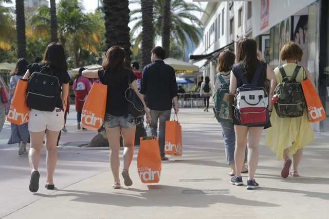 Tourists from Taiwan carry shopping bags as they walk along Lincoln Road Mall, a pedestrian area featuring retail shops and restaurants in Miami Beach, Fla., Feb. 3, 2016. (AP Photo/Lynne Sladky)
