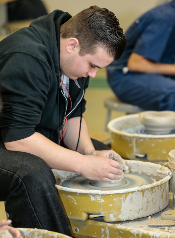 Ceramics student, Zach Grogan, opens the center on a new ceramic bowl he is making for the Empty Bowl event while in class at Green Valley High School Feb. 20, 2015. View file photo