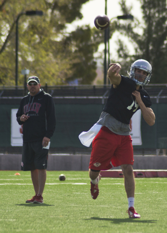 UNLV football head coach Tony Sanchez watches as quarterback Kurt Palandech (14) throws a pass during the first day of spring practice at the Rebel Park practice fields on the UNLV campus in Las V ...