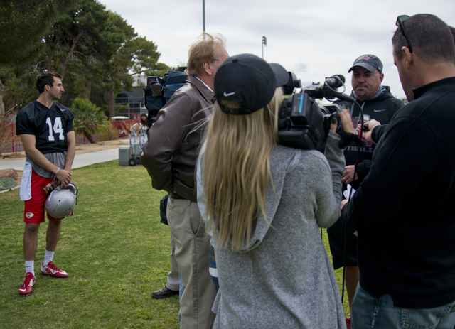 UNLV football head coach Tony Sanchez is interviewed by  media as quarterback Kurt Palandech (14) waits after the first day of spring practice at the Rebel Park practice fields on the UNLV campus  ...