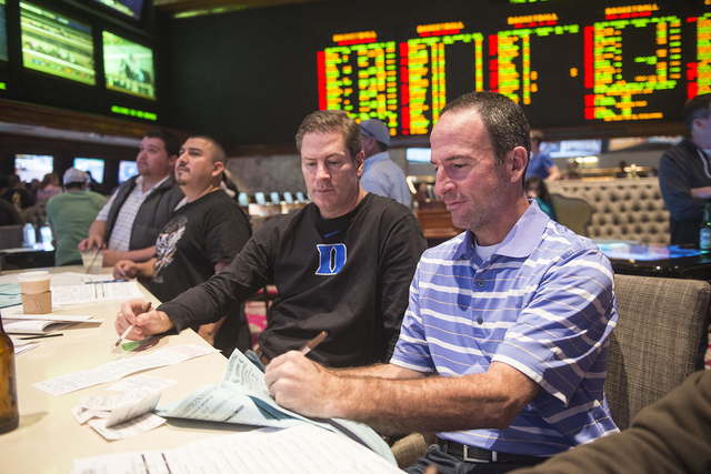 Chuck Andolina, left, and Jeff Reynolds from Dallas place bets on the Super Bowl at the sports book in the Mirage in Las Vegas on Saturday, Jan. 31, 2015. Andolina and Reynolds have traveled to La ...