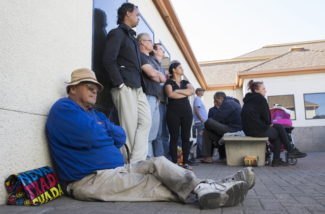 Terry Hess, left, waits in the front of the line for dinner service provided by Friends in the Desert at St. Timothy's Episcopal Church March 22. Benjamin Hager/View
