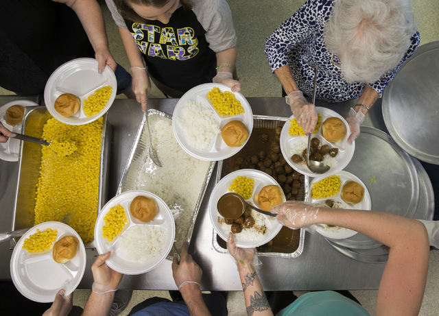 Dinner is prepared by volunteers at Friends in the Desert at St. Timothy's Episcopal Church March 22. Benjamin Hager/View