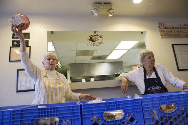 """Muriel Dufendach, operations manager for Friends in the Desert, left, calls tables up to select groceries at St. Timothy's Episcopal Church March 22. """"They are our friends and we treat them like ..."""