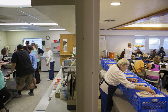 Dinner is prepared, left, in one room while the grocery line is organized by volunteers, right, by Friends in the Desert at St. Timothy's Episcopal Church March 22. Benjamin Hager/View