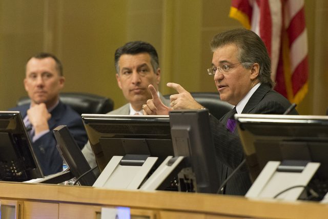 A.G. Burnett, chairman of the Nevada Gaming Control Board, left, and Nevada Governor Brian Sandoval, center, listen as Tony Alamo, chairman of the Nevada Gaming Control Board are seen at the Nevad ...