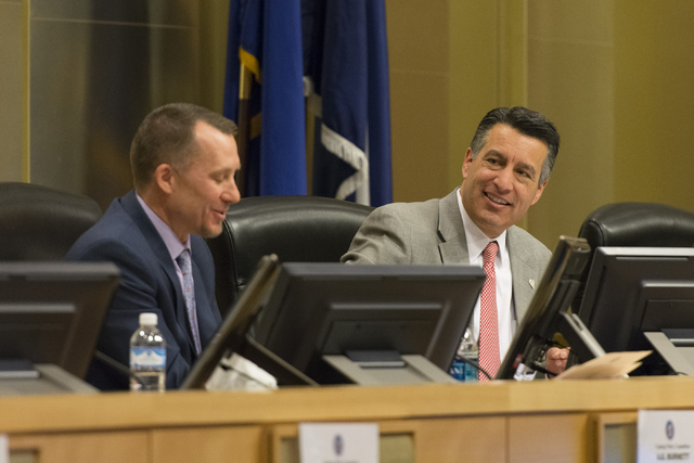 A.G. Burnett, chairman of the Nevada Gaming Control Board, left, and Nevada Governor Brian Sandoval speak at the Nevada Gaming Policy Committee meeting at Las Vegas City Hall Council Chambers Mond ...