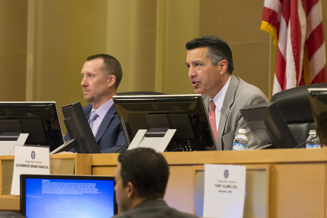 A.G. Burnett, chairman of the Nevada Gaming Control Board, left, and Nevada Governor Brian Sandoval listen as David Schwartz, director of  Center for Gaming Research, speaks at the Nevada Gaming P ...