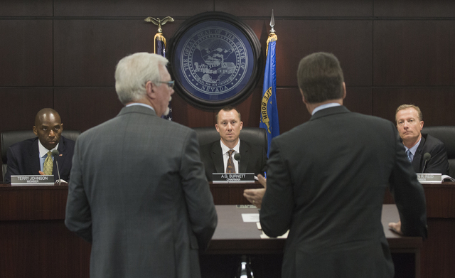 Nevada Gaming Control members Terry Johnson, left, A.G. Burnett, chairman, and Shawn Reid listens while Caesars Entertainment Corp. CEO Mark Frissora, in foreground on right, speaks while seeking  ...