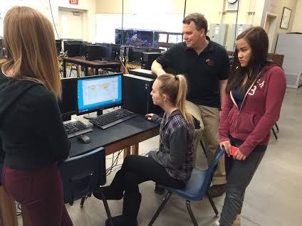 Emma Hirsch, left, watches as Hailey Jones, seated, pulls up a map for GIS teacher Jeff Gromny and Ellyz Ball at West Career and Technical Academy Jan. 26. Jan Hogan/View