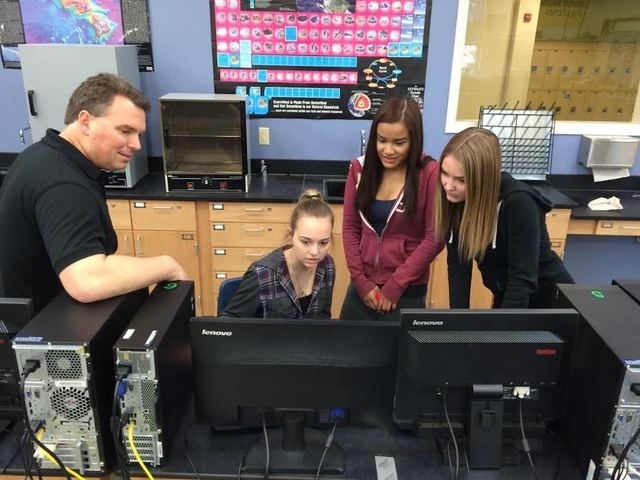 West Career and Technical Academy GIS teacher Jeff Gromny, far left, watches as Hailey Jones, seated, pulls up a map for fellow students Ellyz Ball and Emma Hirsch on Jan. 26 at the school, 11945  ...