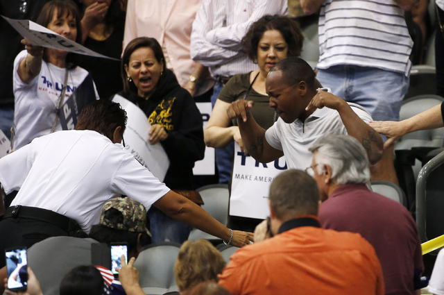 A supporter of Republican presidential candidate Donald Trump, right, shouts and gestures to a protester, on the ground and not seen, as they scuffle as Trump speaks during a campaign rally Saturd ...