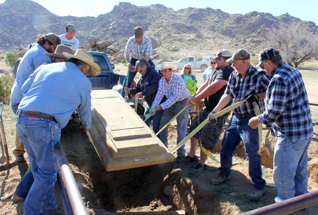 A group of volunteers lower a concrete lid over the restored grave of Arthur Coleman at the Gold Butte ghost town site 100 miles northeast of Las Vegas Saturday, March 26, 2016. The remains of Col ...