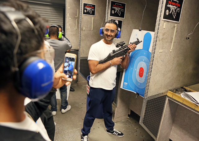 Purdip Lall, center, poses for a personal photo with a MP5 submachine gun and his target at The Gun Storeճ indoor range Monday, March 21, 2016, in Las Vegas. Lall was with a group from Engla ...