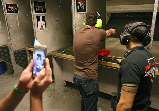 Nicholas DiSanto, center, of Brooklyn, New York, shoots a handgun and has his video taken by a friend at The Gun Storeճ indoor range Monday, March 21, 2016, in Las Vegas. Worker Ketzu Flores ...