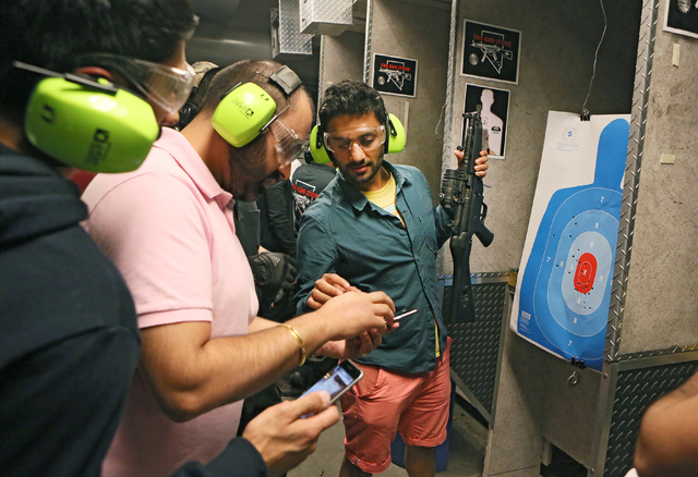 Mak Singh, right, holds a MP5 submachine gun and assists friend Kam Bharj, second from left, with a cell phone before posing for a personal photo The Gun Storeճ indoor range Monday, March 21 ...