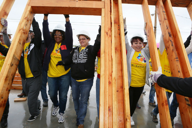Joanne Langston-Hendrickson, center, joins volunteers in raising the first wall of her new home during a Habitat for Humanity Las Vegas home building and celebration event Jan. 31, 2015, in Hender ...