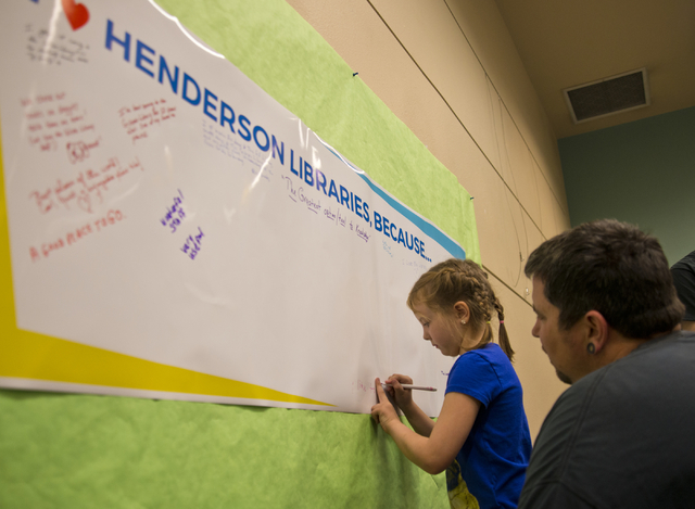 Aisleigh King leaves a message on a poster as her father, Cameron, helps during an event featuring the new Henderson Libraries' website and logo at the Green Valley Library March 1. Daniel Clark/View