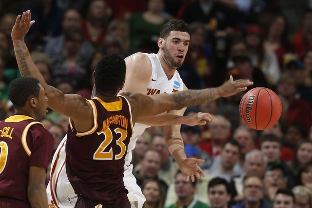 Iowa State forward Georges Niang, back, passes the ball by Iona forward Jordan Washington in the second half of a first-round men's college basketball game Thursday, March 17, 2016, in the NCAA To ...
