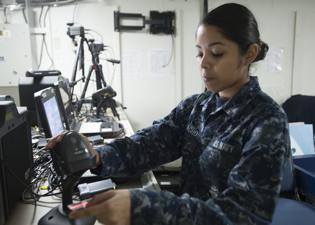 Personnel Specialist Seaman Apprentice Jessica Camacho of Las Vegas scans a common access card in December 2015 while making a new ID for a sailor aboard the U.S. Navy's only forward-deployed airc ...