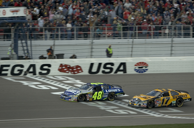 Jimmie Johnson takes the checkered flag a few feet ahead of Matt Kenseth in the NASCAR Nextel Cup UAW-DaimlerChrysler 400 at Las Vegas Motor Speeway Sunday, March 12, 2006. (K.M. Cannon/Las Vegas  ...