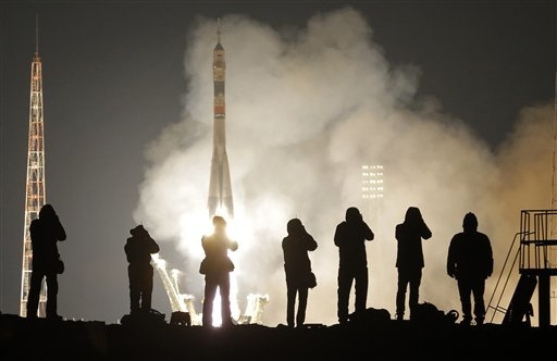 Journalists take photos of the Soyuz-FG rocket booster with Soyuz TMA-20M capsule carrying a new crew to the International Space Station, ISS, blasting off at the Russian leased Baikonur cosmodrom ...
