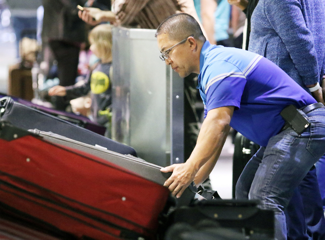 Mits Ohata, of Stockton, Calif., retrieves luggage at a Southwest Airlines baggage claim at McCarran International Airport Wednesday, March 23, 2016, in Las Vegas. Ronda Churchill/Las Vegas Review ...