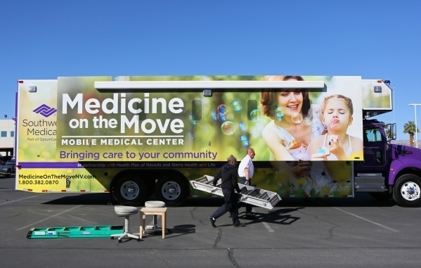 Southwest Medical Associates employees Erwin Drown, left, and Chris Philips set up a new mobile medical center outside UnitedHealthcare/Southwest Medical Associates headquarters Feb. 22. The 45-fo ...