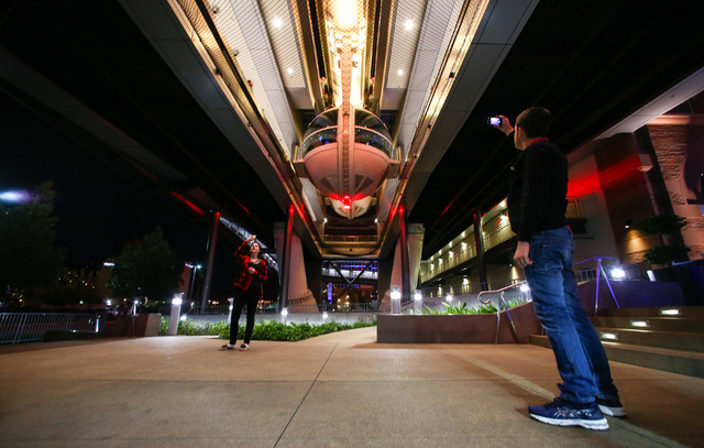 People take photos of the High Roller, lit up as the colors of the flag of Belgium following the Brussels attacks, at the Linq in Las Vegas on Tuesday, March 22, 2016. Chase Stevens/Las Vegas Revi ...