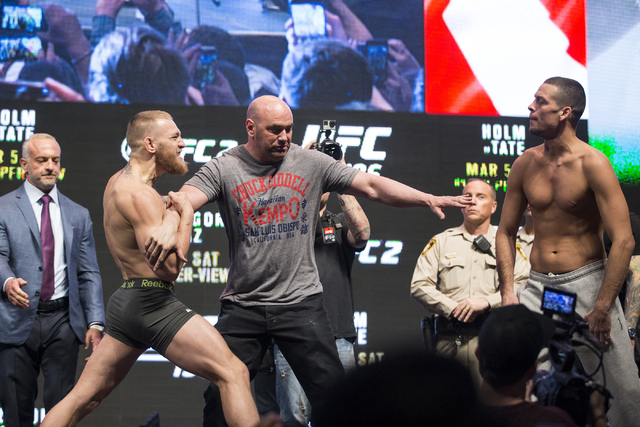 UFC fighters Conor McGregor, left, and Nate Diaz, right, are separated by UFC president Dana White while their face off in the UFC 196 weigh-in event at the MGM Grand Garden Arena on Friday, March ...