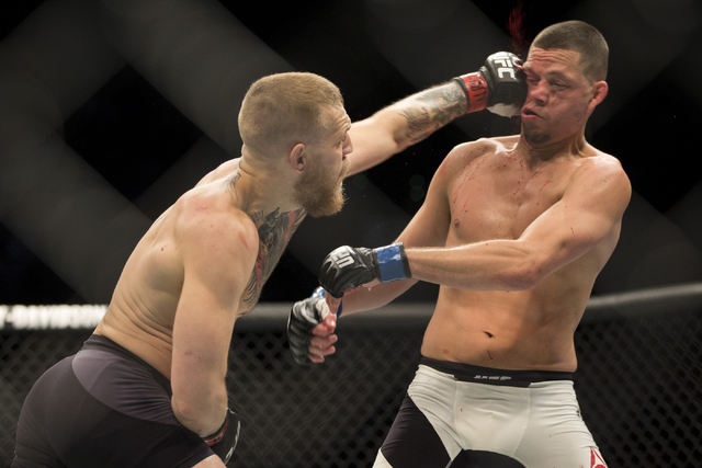 Conor McGregor, left, connects a left punch against Nate Diaz in the menճ welterweight bout during UFC 196 at MGM Grand Garden ArenaSaturday, March 5, 2016, in Las Vegas. Diaz won way of sub ...