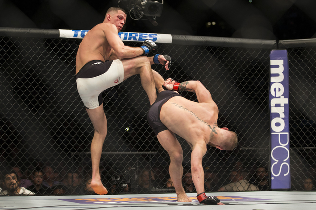 Nick Diaz, left, defends against a kick against Conor McGregorin their menճ welterweight bout during UFC 196 at MGM Grand Garden ArenaSaturday, March 5, 2016, in Las Vegas. Diaz won way of s ...