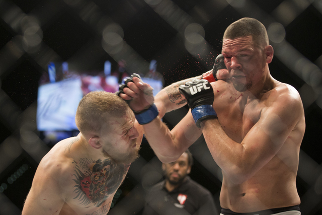 Conor McGregor, left, connects a left punch against Nate Diaz in their menճ welterweight bout during UFC 196 at MGM Grand Garden ArenaSaturday, March 5, 2016, in Las Vegas. Diaz won way of s ...