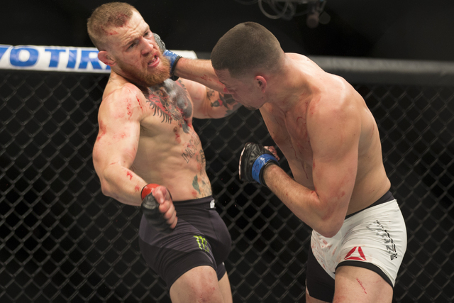 Nate Diaz, right, connects a right punch against Conor McGregor in their menճ welterweight bout during UFC 196 at MGM Grand Garden ArenaSaturday, March 5, 2016, in Las Vegas. Diaz won way of ...