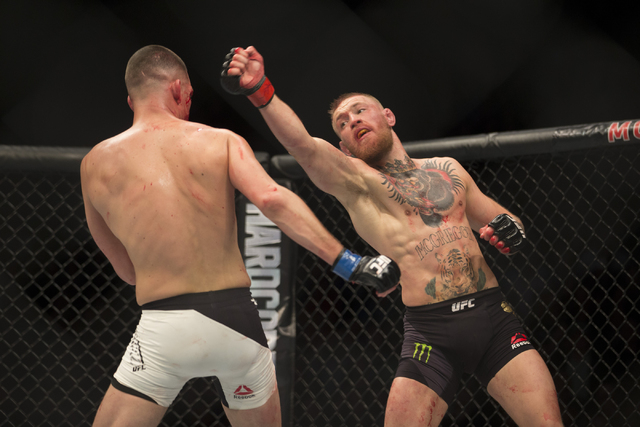 Conor McGregor, right, throws a punch against Nate Diaz in the menճ welterweight bout during UFC 196 at MGM Grand Garden ArenaSaturday, March 5, 2016, in Las Vegas. Diaz won way of submissio ...