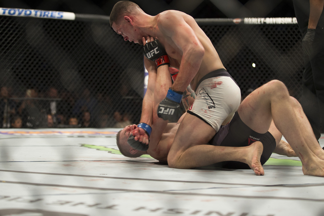 Nate Diaz, top, throws a punch against Conor McGregor in their menճ welterweight bout during UFC 196 at MGM Grand Garden ArenaSaturday, March 5, 2016, in Las Vegas. Diaz won way of submissio ...