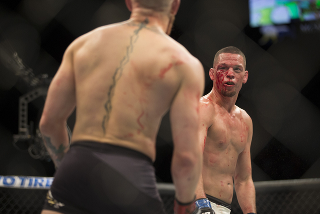 Conor McGregor, left, battles against Nate Diaz in their menճ welterweight title bout during UFC 196 at MGM Grand Garden Arena on Saturday, March 5, 2015 in Las Vegas. Diaz won by way of sub ...