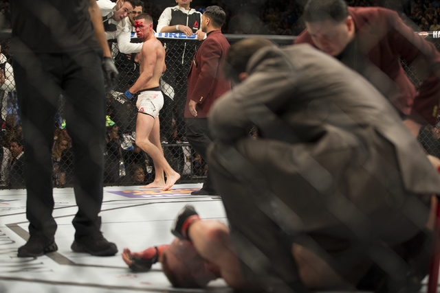 Nate Diaz, left, looks at Conor McGregor after winning in their menճ welterweight title bout during UFC 196 at MGM Grand Garden Arena on Saturday, March 5, 2015 in Las Vegas. Diaz won by way ...
