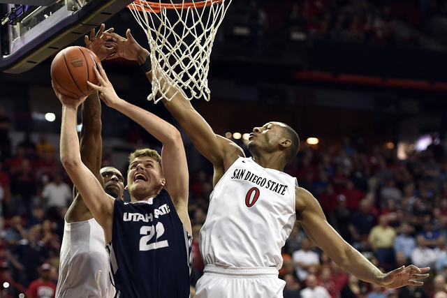 Utah State's Quinn Taylor (22) shoots against San Diego State's Winston Shepard (13) and Skylar Spencer (0) during the second half of an NCAA college basketball game at the Mountain West Conferenc ...