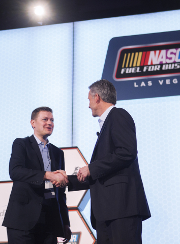 Steve Phelps, chief marketing officer for NASACR, left, shakes hands with Brian Davis, vice president of business development at Allegiant, during a press conference to announce a new sponsorship  ...