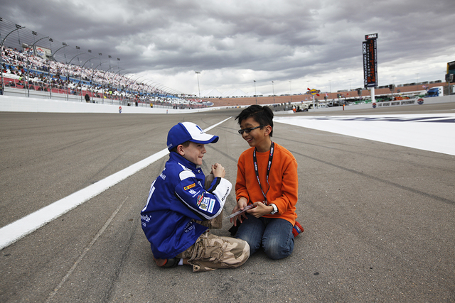 Chase Gibson,11, and Dyan Leongill, 11, talk as they sit on the race track before the start of the Kobalt 400 at Las Vegas Motor Speedway in Las Vegas Sunday, March. 6, 2016. Rachel Aston/Las Vega ...