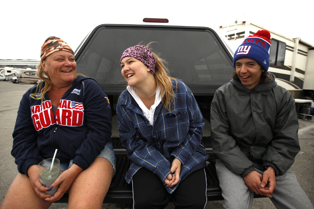 Gina Perry, from left, her daughter Madison Perry, and their friend Nick Teague wait at their trailer site before the start of the Kobalt 400 at Las Vegas Motor Speedway in Las Vegas Sunday, March ...