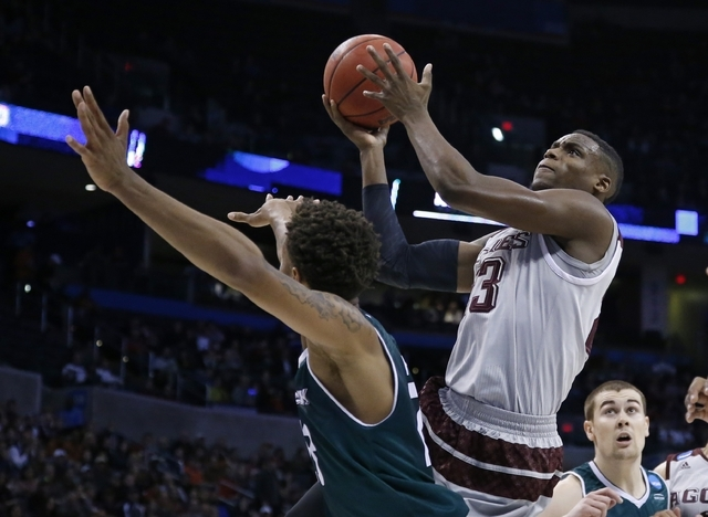 Texas A&M guard Danuel House, right, shoots over Green Bay forward Jamar Hurdle, left, in the first half of a first-round men's college basketball game in the NCAA Tournament, Friday, March 18 ...