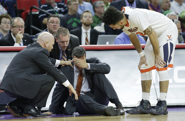 Virginia head coach Tony Bennett is attended to after he collapsed during play against Hampton during the first half of a first-round men's college basketball game in the NCAA Tournament, Thursday ...