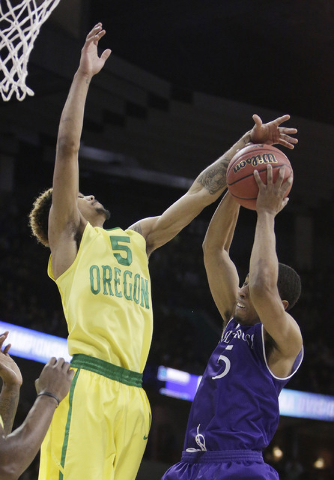 Oregon guard Tyler Dorsey, left, and Holy Cross guard Cullen Hamilton go after a rebound during the first half of a first-round men's college basketball game in the NCAA Tournament in Spokane, Was ...